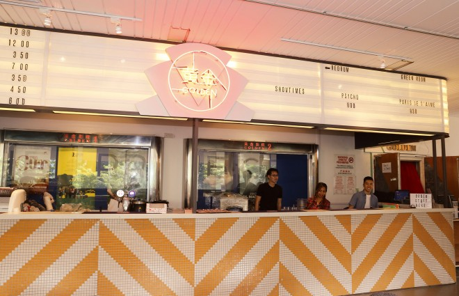 上映時間の掲示も昔の映画館のようなレトロな雰囲気。フロアにはカフェがあり、食事やビール、ワインも楽しめる。